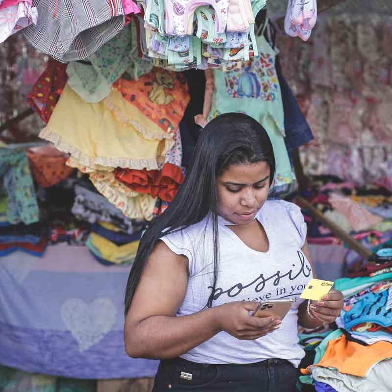 Consumidora alt.bank com cartão na mão